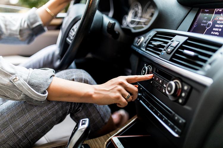 car-dashboard-radio-closeup-woman-sets-up-radio-while-driving-car.jpg